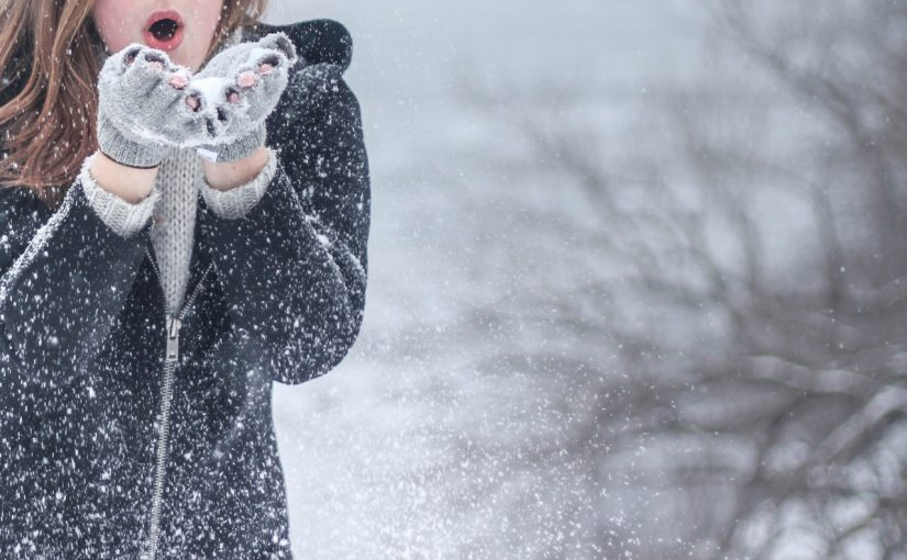 Young woman blowing snow toward camera on winter background